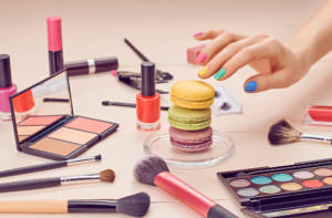Still life, fashion woman essentials cosmetics. Beauty makeup accessories. Macarons french dessert. Lipstick, brushes, eyeshadow, mascara, hand colorful nails. Unusual creative set.Vanilla background